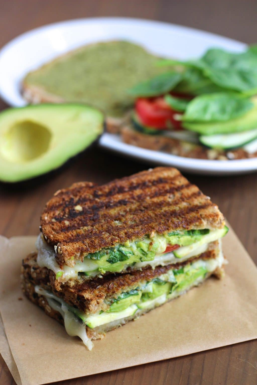 A vegan sandwich cut in half and stacked on top of each other on top of a piece of parchment paper next to a white plate and an avocado.