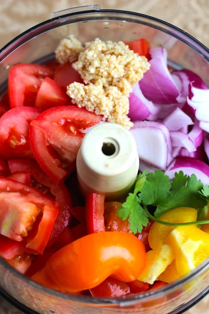 A food processor bowl filled with the ingredients to make salsa.
