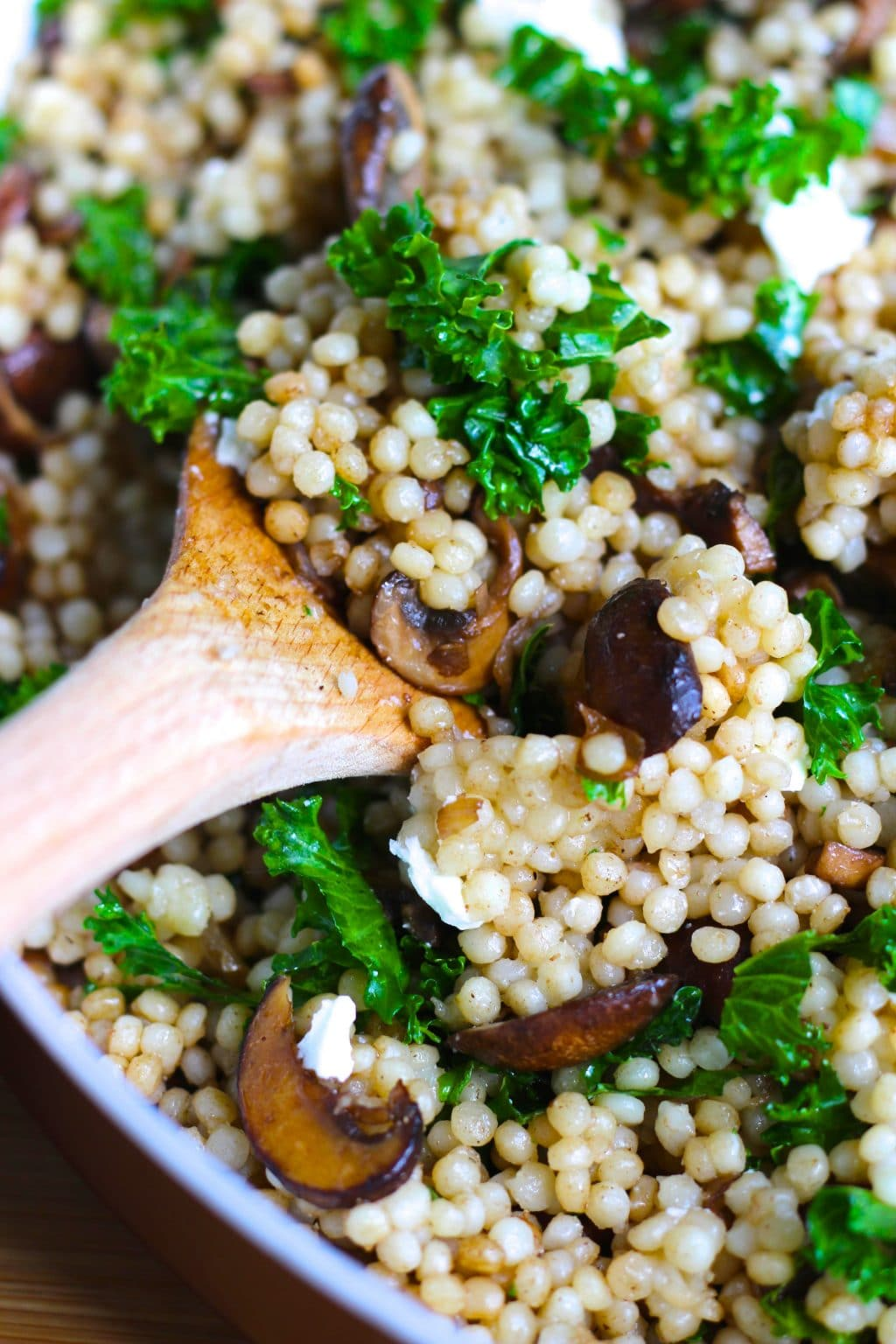 A wooden spoon scooping mushroom couscous out of a pan.