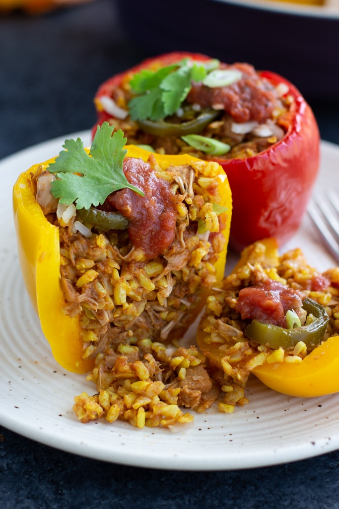 A yellow vegan stuffed pepper that is cut in half and the filling is falling out. There is also a full red stuffed pepper behind it sitting on a white textured plate.