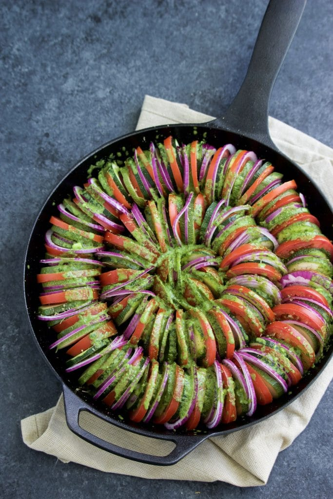 Overhead shot of sliced vegetables topped with pesto in a cast iron pan on a dark background.