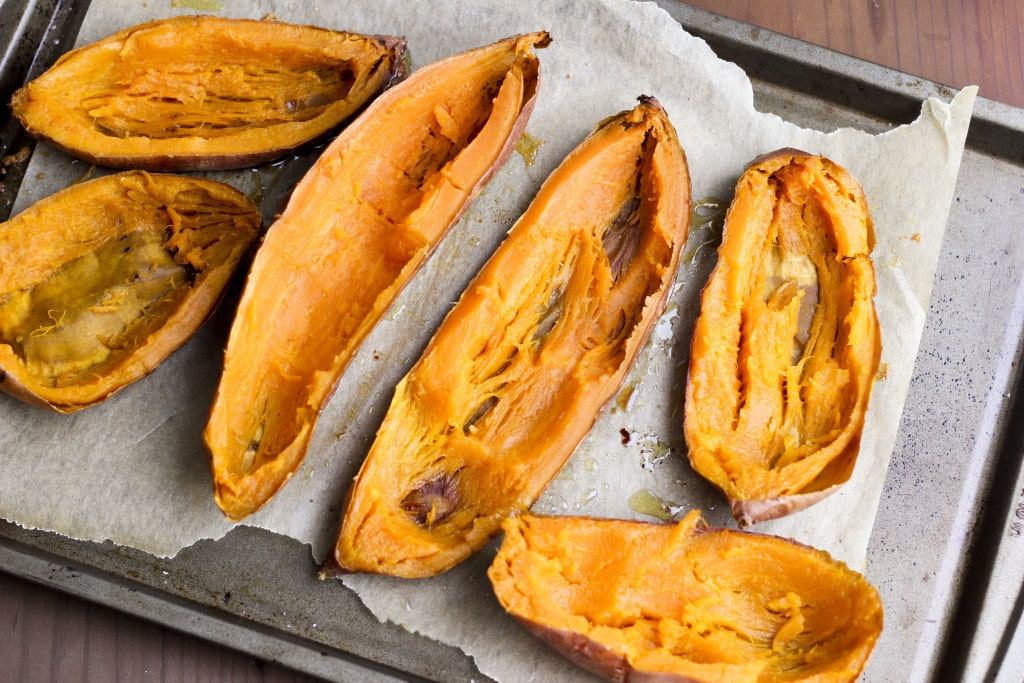A baking tray filled with six sweet potato halves that have been scooped out.