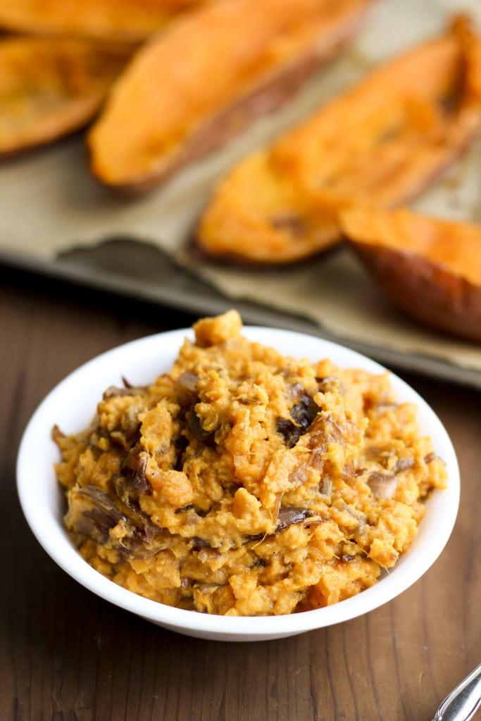 A white bowl filled with mashed sweet potatoes on a rustic background.