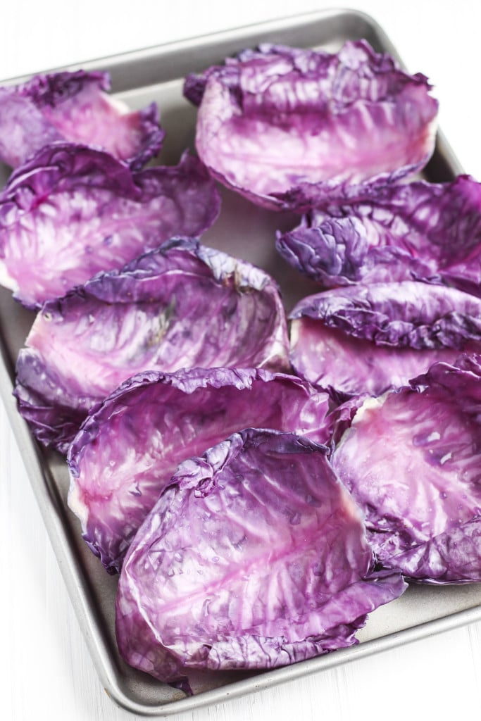 A tray full of cooked red cabbage leaves on a white background.