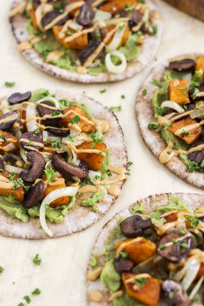 Multiple pita wraps topped with roasted vegetables and sauce on a light background.