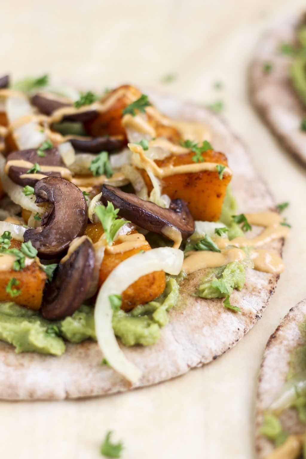 A close up view of a pita topped with roasted vegetables, mashed avocado, and sauce.