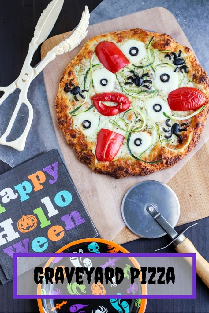 A pizza on a cutting board next to a pizza cutter, halloween napkin, and skeleton tongs.