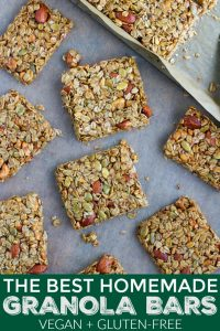 A large tray of multiple homemade vegan granola bars that are loaded with nuts and seeds.
