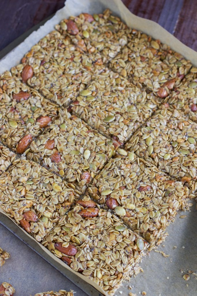 A full tray of freshly baked granola bars on a parchment-lined tray.