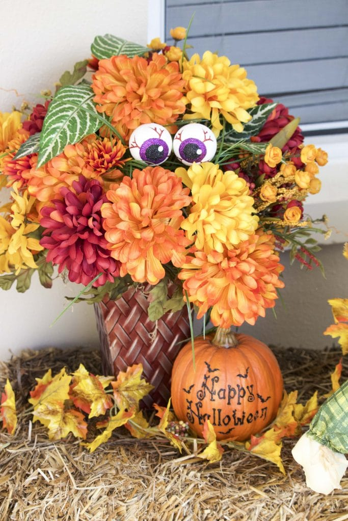 A fall-themed flower arrangement decorated for Halloween with eyeballs and a pumpkin on top of a hay bale.