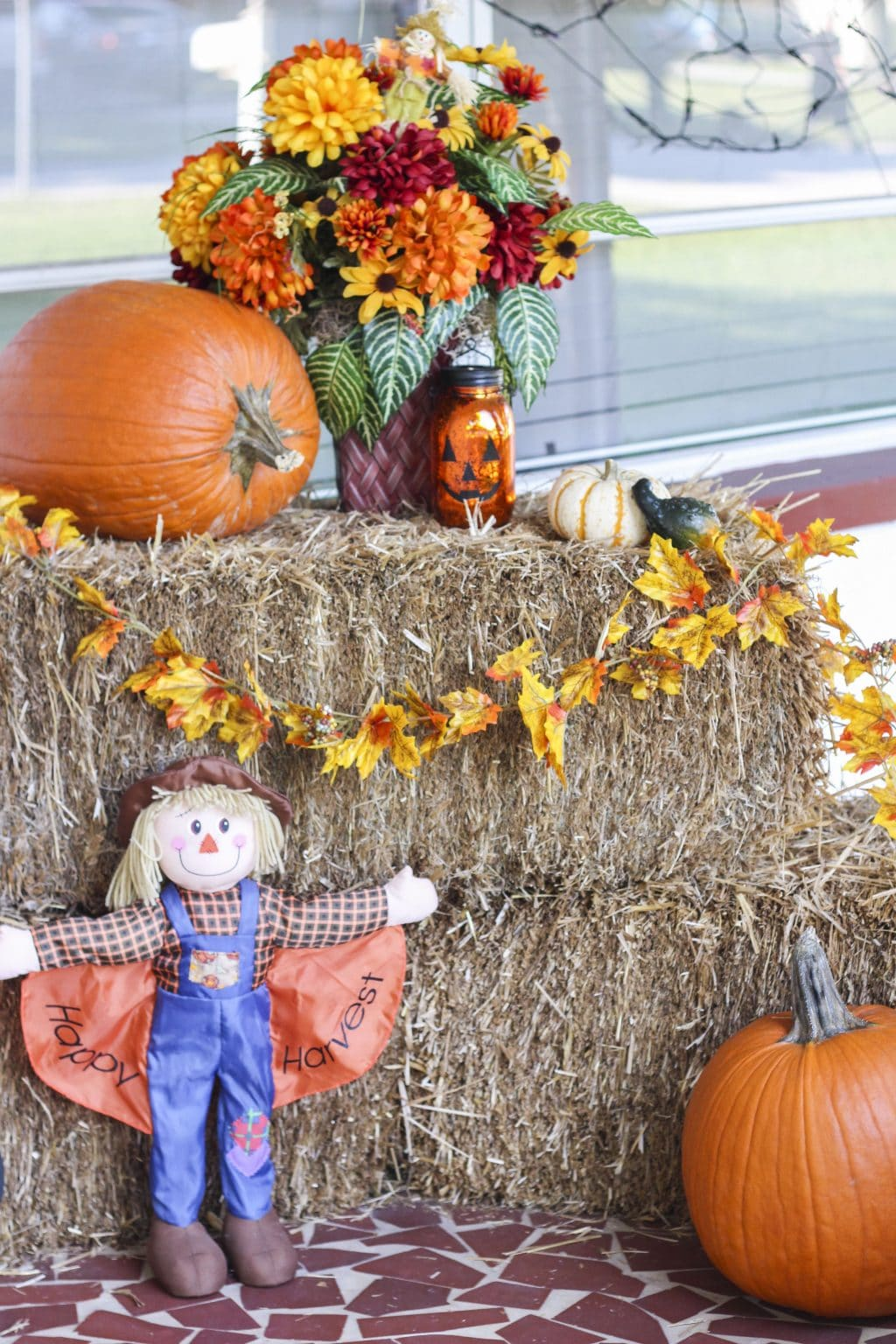 A fall front porch display with flowers, pumpkins, a scarecrow and fall decor.