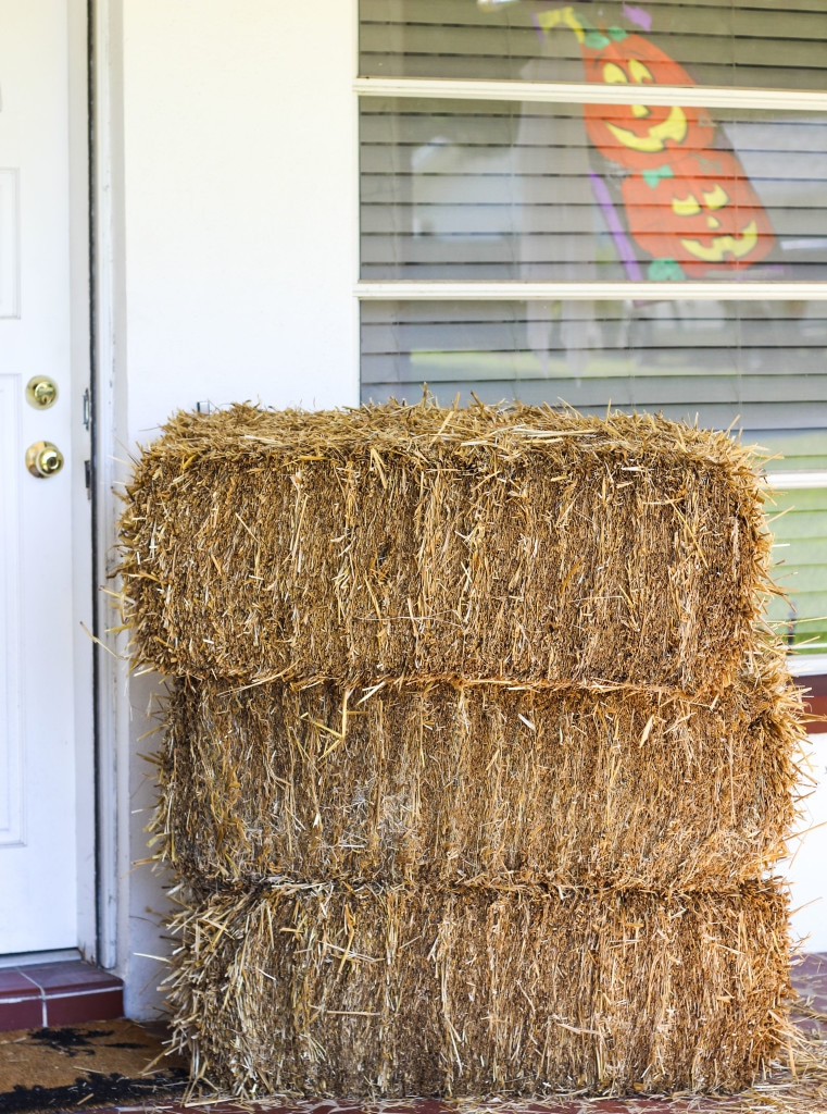 A stack of three hay bales on top of each other next to a front door.