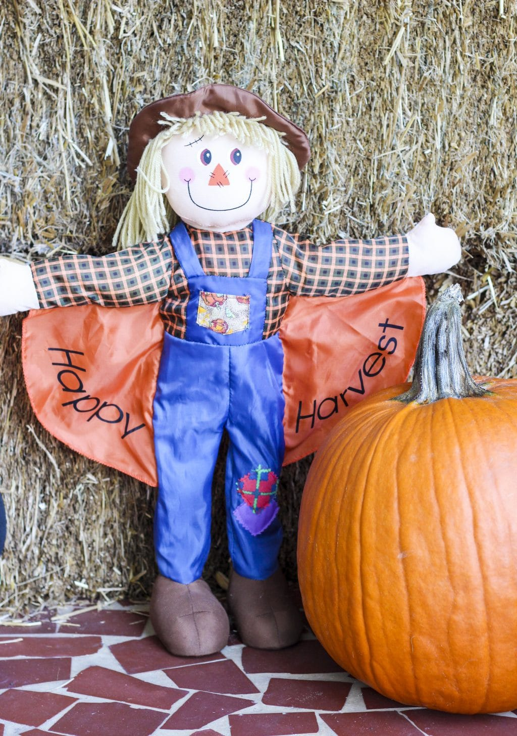 A large scarecrow next to a pumpkin a hay bale.