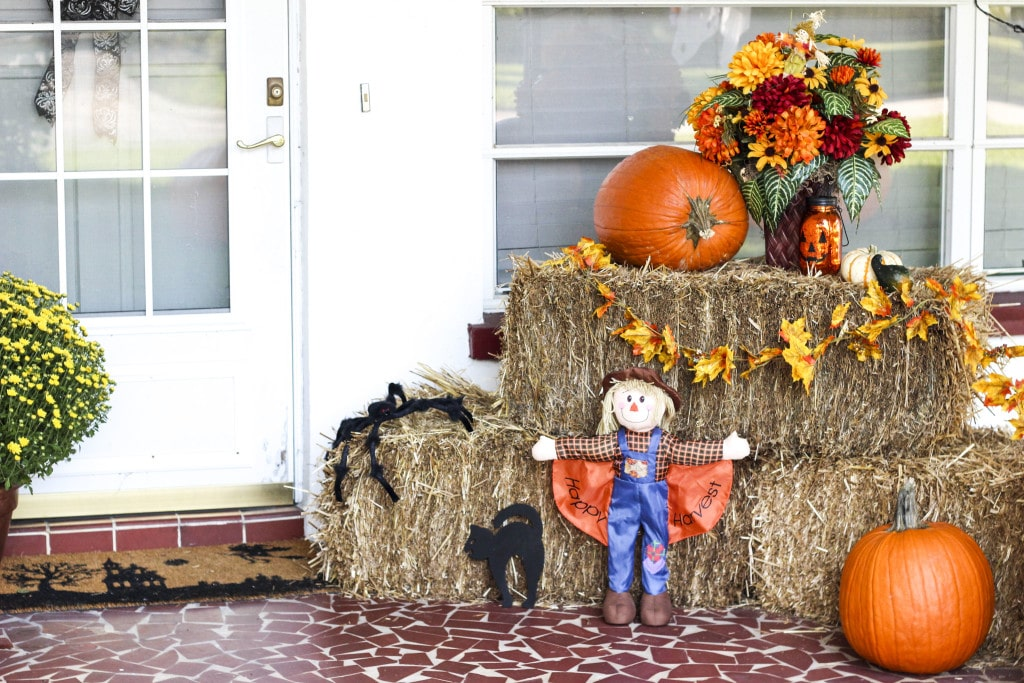 A front porch decorated with fall decor of hay bales, pumpkins, a scarecrow, and flowers!
