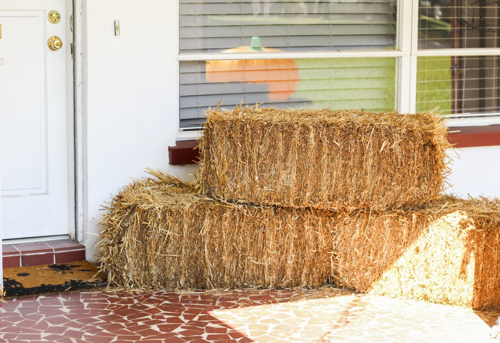 Three hay bales stacked in a V shape on a front porch patio.
