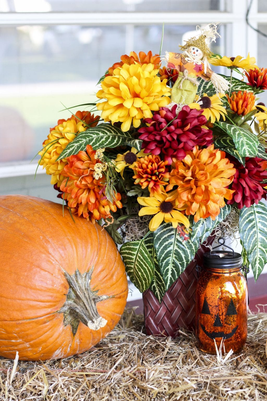A large pumpkin, flower arrangement, and pumpkin mason jar on top of a hay bale.
