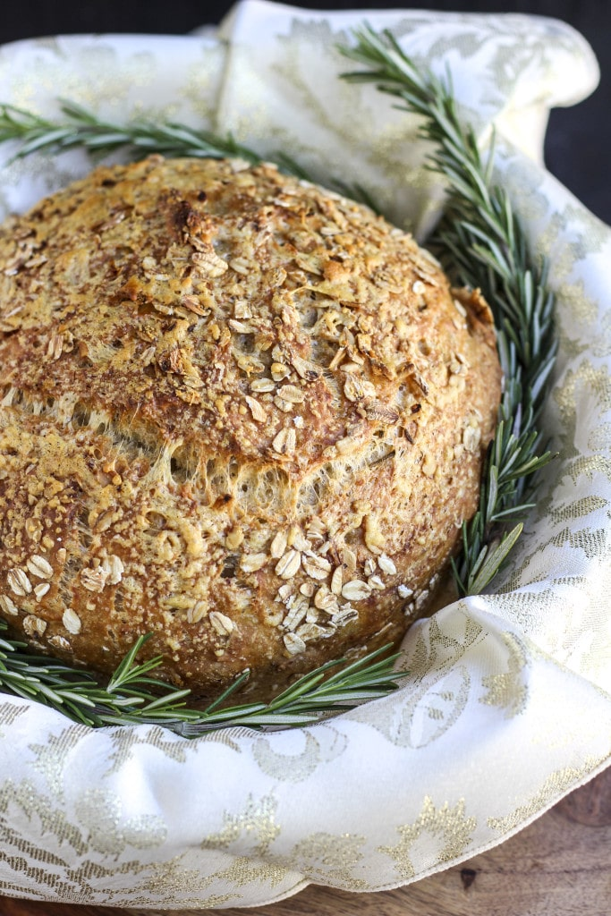 A loaf of vegan rosemary bread in a basket with a few sprigs of fresh rosemary.