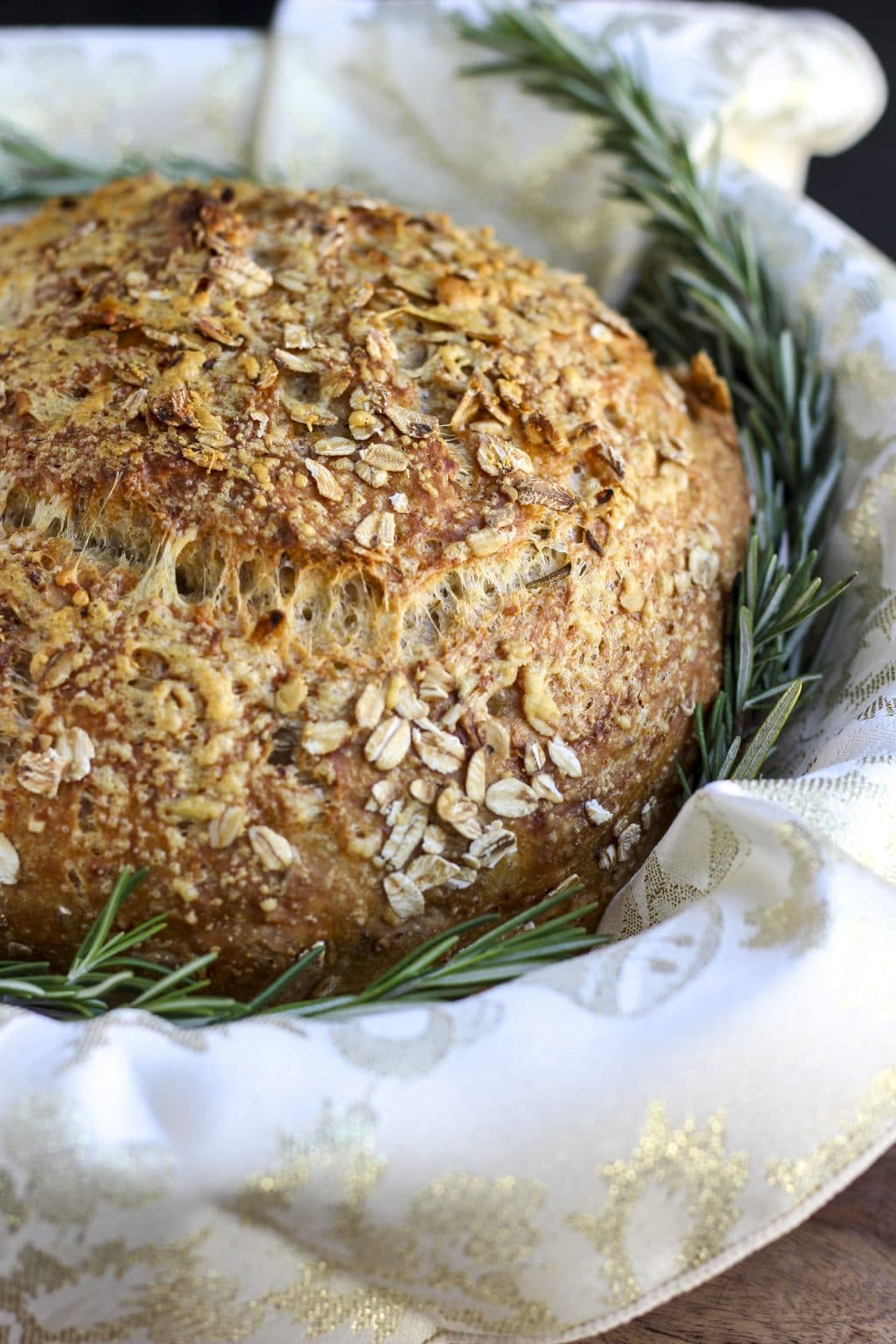 A loaf of bread in a towel lined basket with fresh rosemary springs tucked around it.