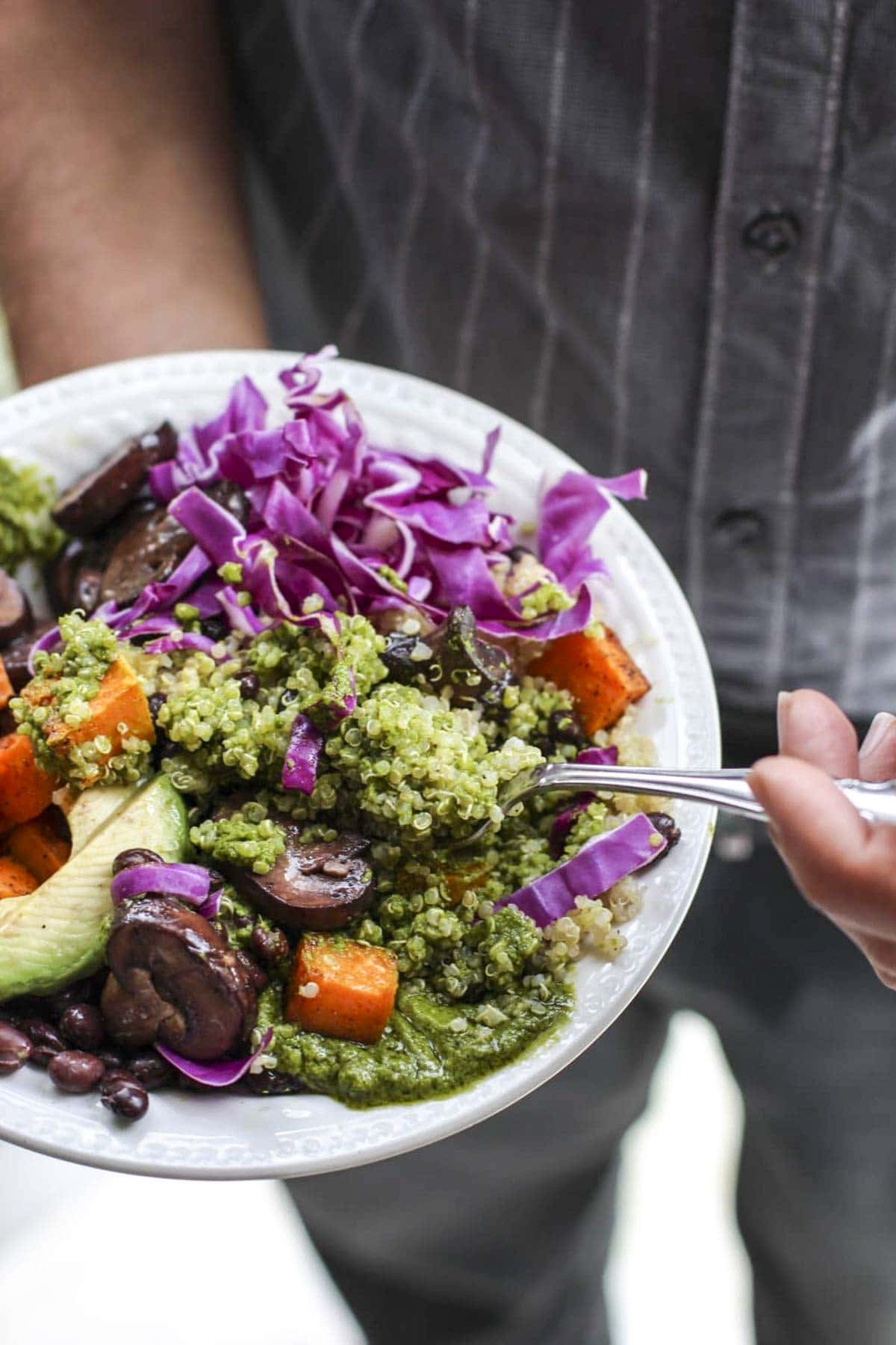 A pan holding a white bowl filled with vegetables, quinoa, and green pistachio sauce.