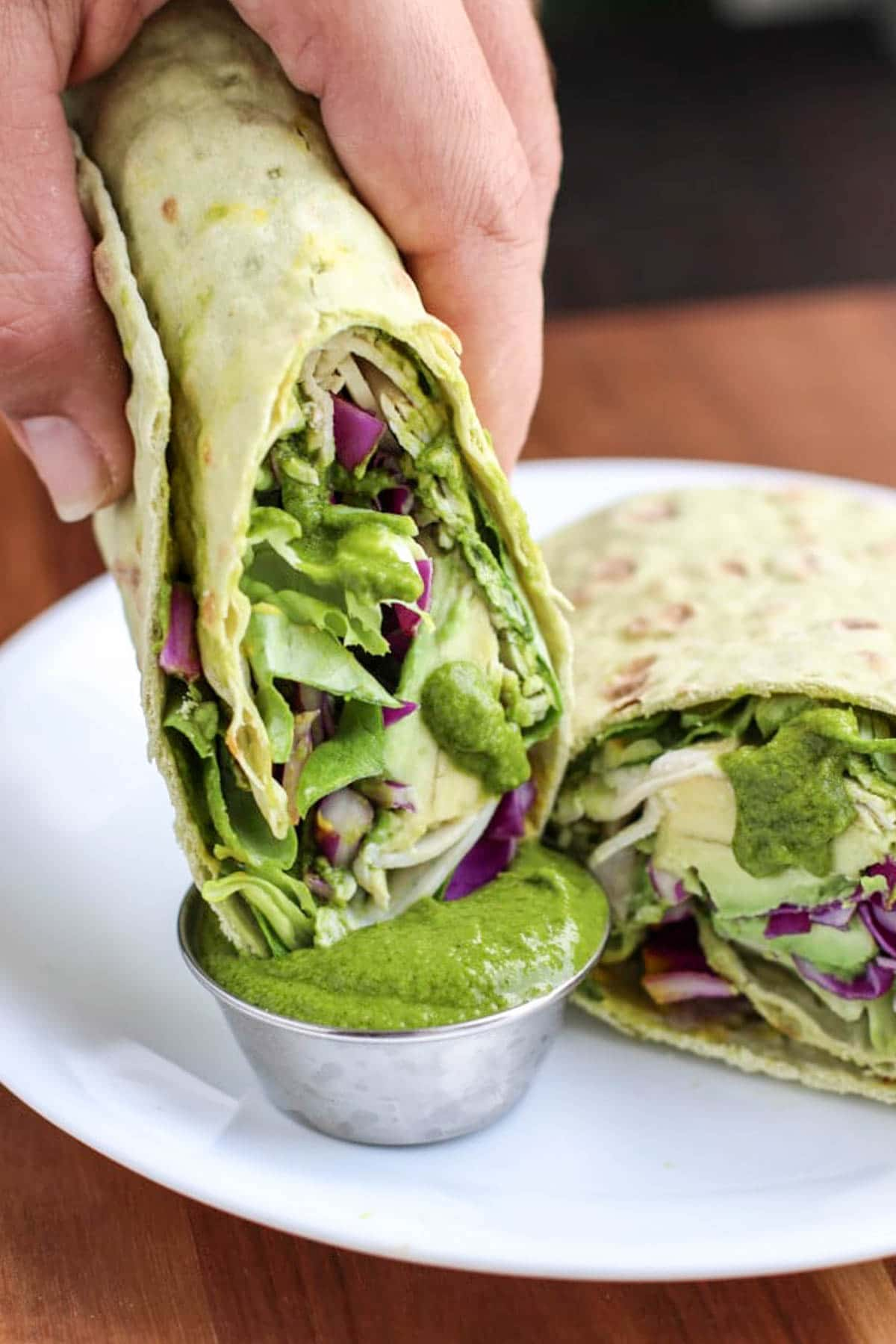 A hand dipping half a wrap into green sauce on a white plate.