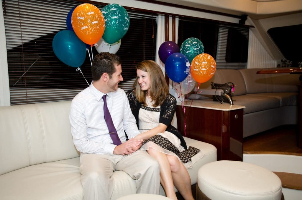 A young man and woman smiling while looking at each other next to balloons.