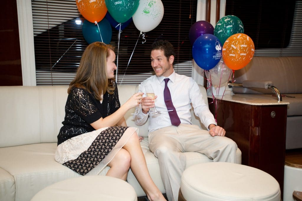 A man and a woman toasting each other next to balloons on the Grand 1 Yacht.