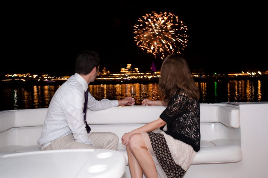 A young man and woman watching the Magic Kingdom fireworks from the Grand 1 Yacht.
