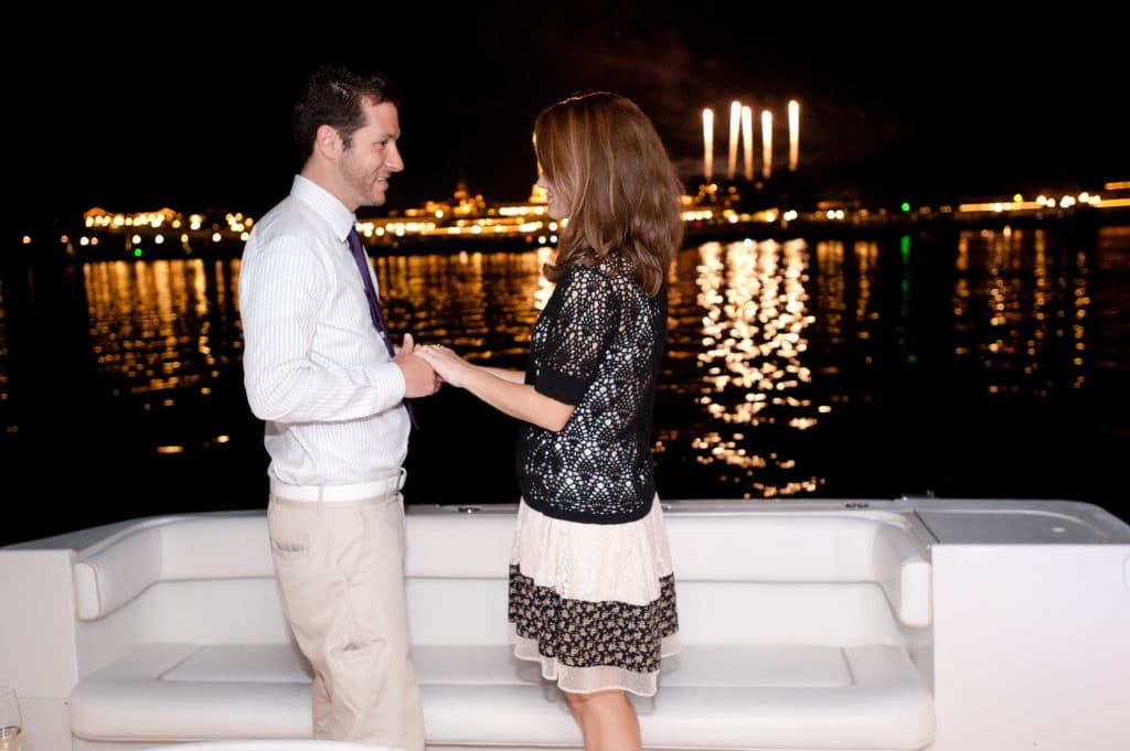 A young man proposing to a young woman on the seven seas lagoon.