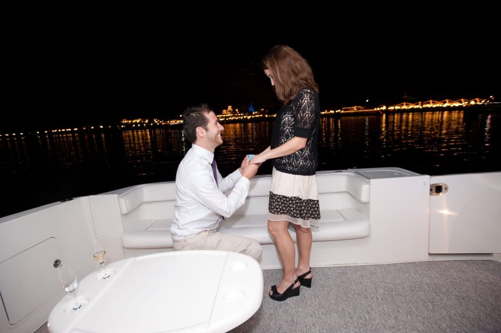 A young man kneeling and proposing to a young woman on the Grand 1 Yacht in Disney World.