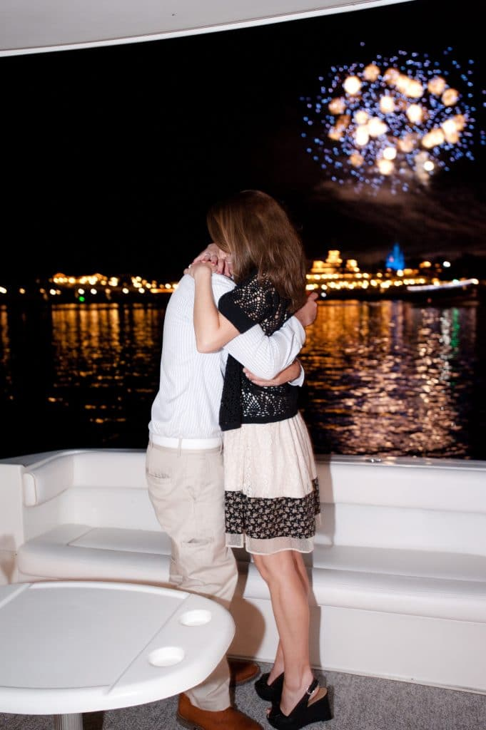 A young couple embracing after getting engaged on the Grand 1 Yacht in Disney World.