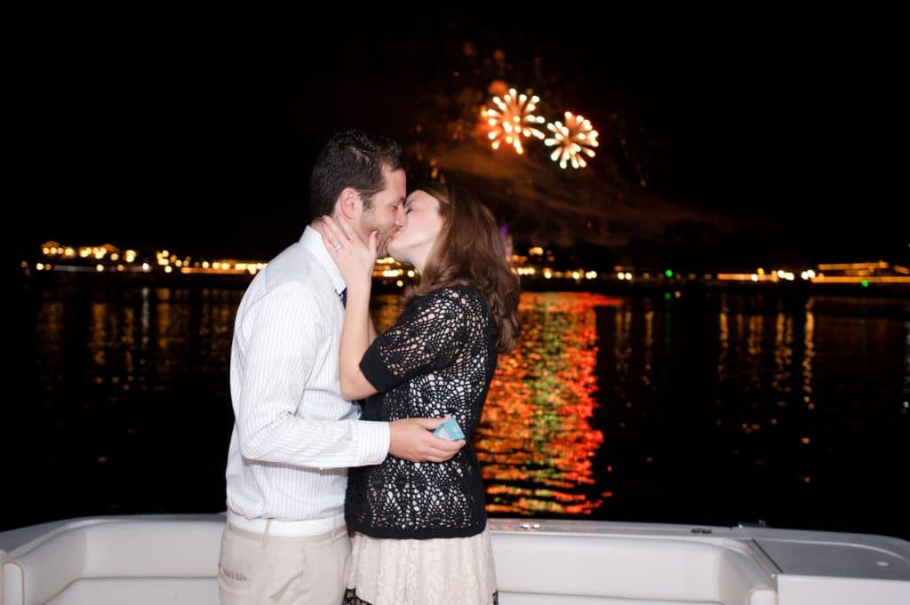 A young man and woman kissing during the fireworks after a Disney engagement.