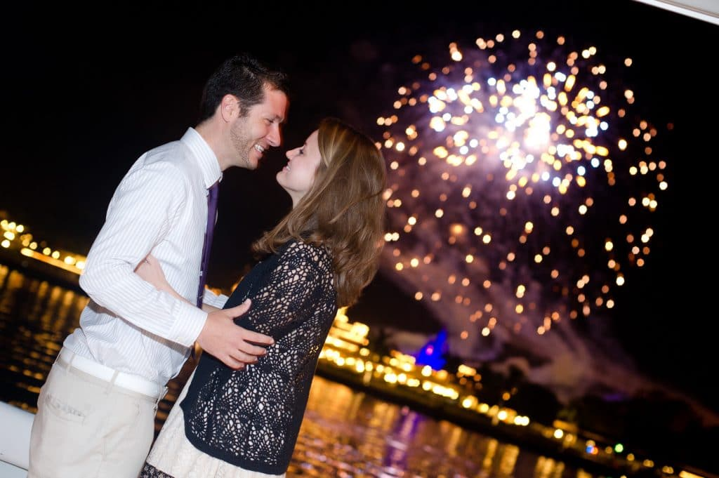 A young man and woman embracing after a Disney proposal during the fireworks.