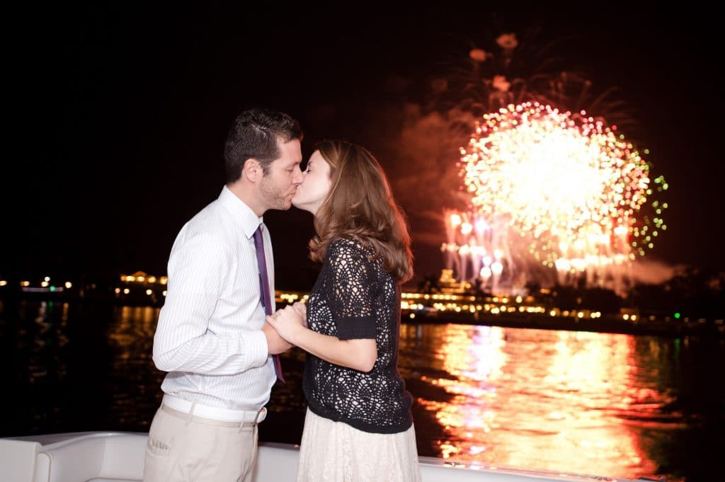 A young man and woman kissing after a Disney engagement during the fireworks on the Grand 1 Yacht.