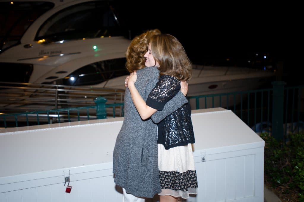 A young woman hugging her mother in front of a white box on the Grand Floridian dock.