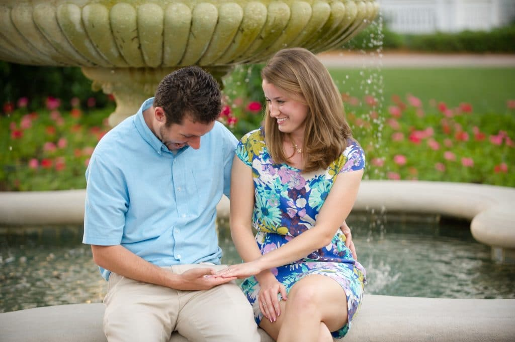 A young man and woman sitting on a fountain ledge looking happy.