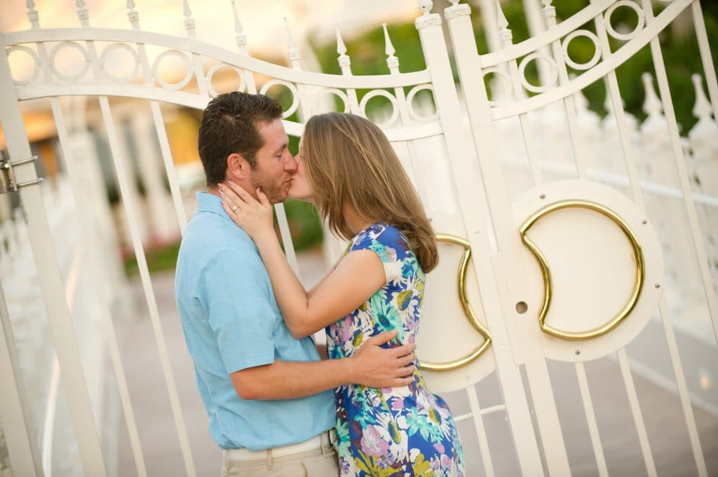 A young couple kissing in front of the gates of the Grand Floridian wedding pavilion.