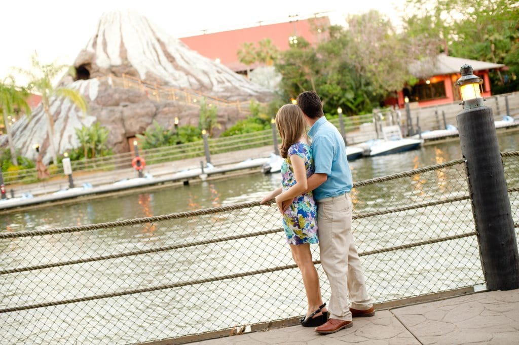 A young man and woman looking out over the water at the Polynesian Resort in Disney World.