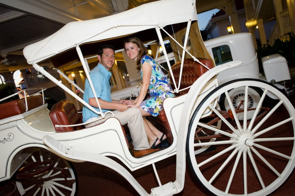 A young man and woman holding hands and sitting in the coach at the Grand Floridian Resort.