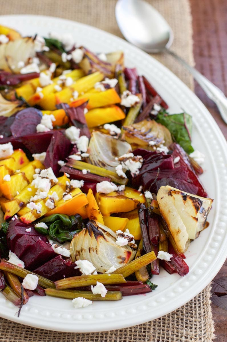 Side view of a white platter filled with roasted beet salad.