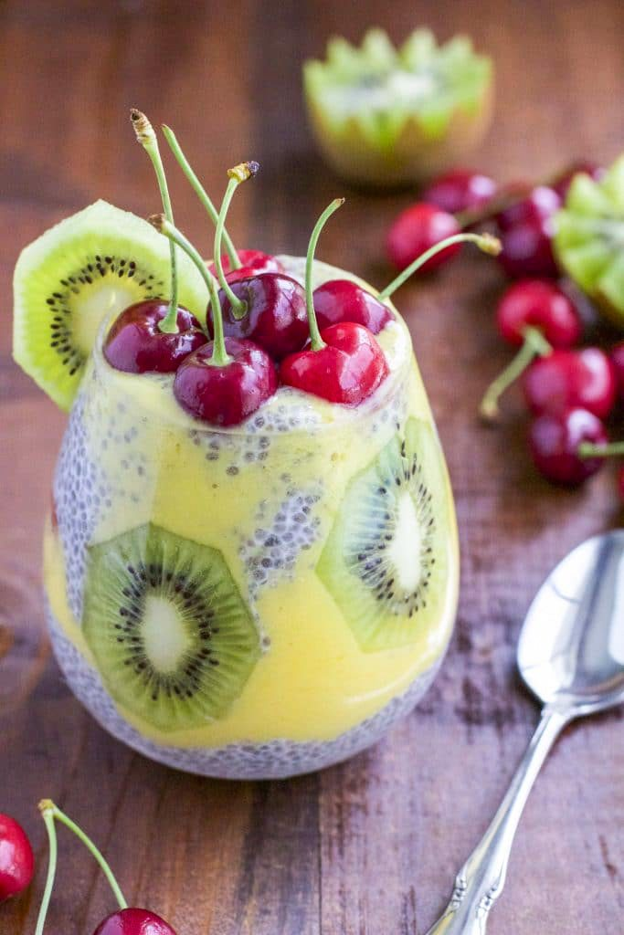 A cup filled with chia seed pudding and fruit on a wooden table top.
