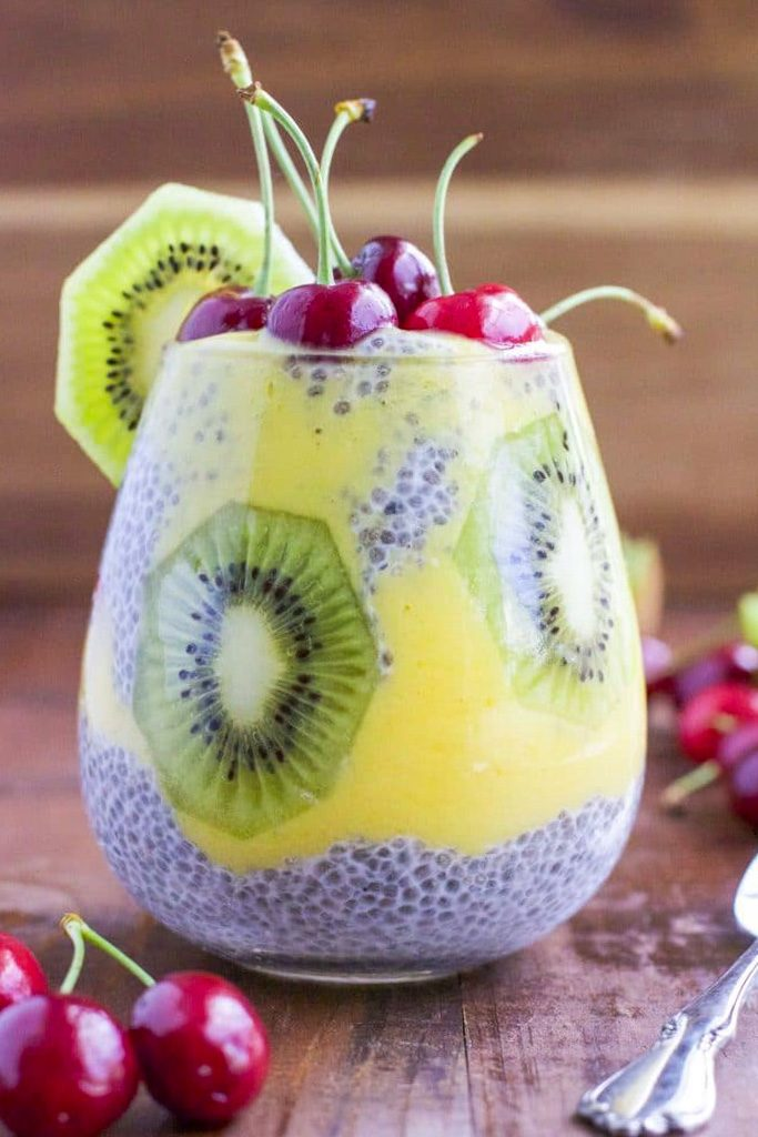 A cup filled with chia seed pudding and fruit with a rustic wood background.