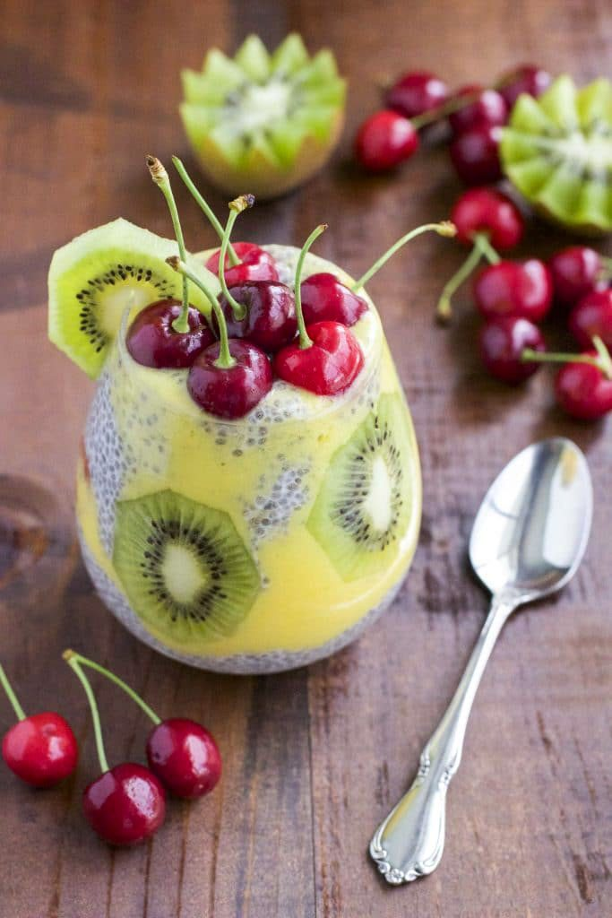 A cup filled with pudding and fruit next to fresh fruit on a wood table top.