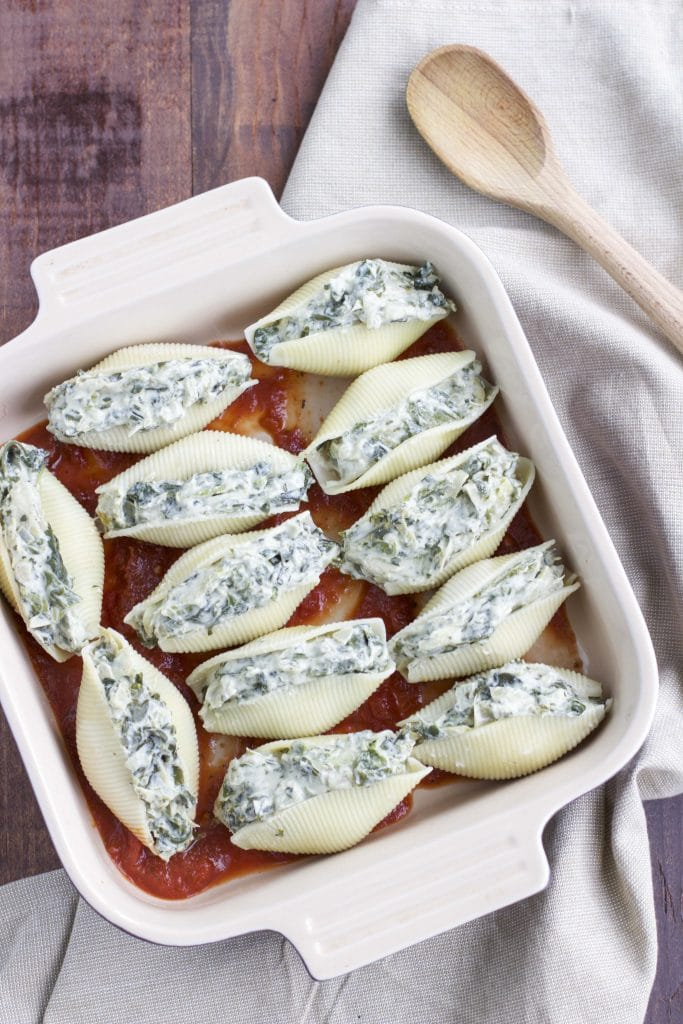 Vegan stuffed shells in a square casserole dish on a nude napkin next to a wooden spoon on a rustic background.