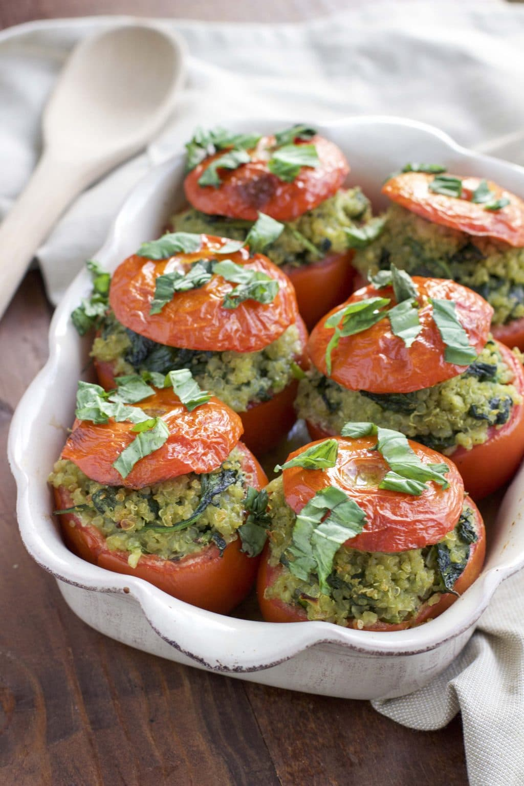 Roasted stuffed pesto tomatoes in a white casserole dish on a rustic background.