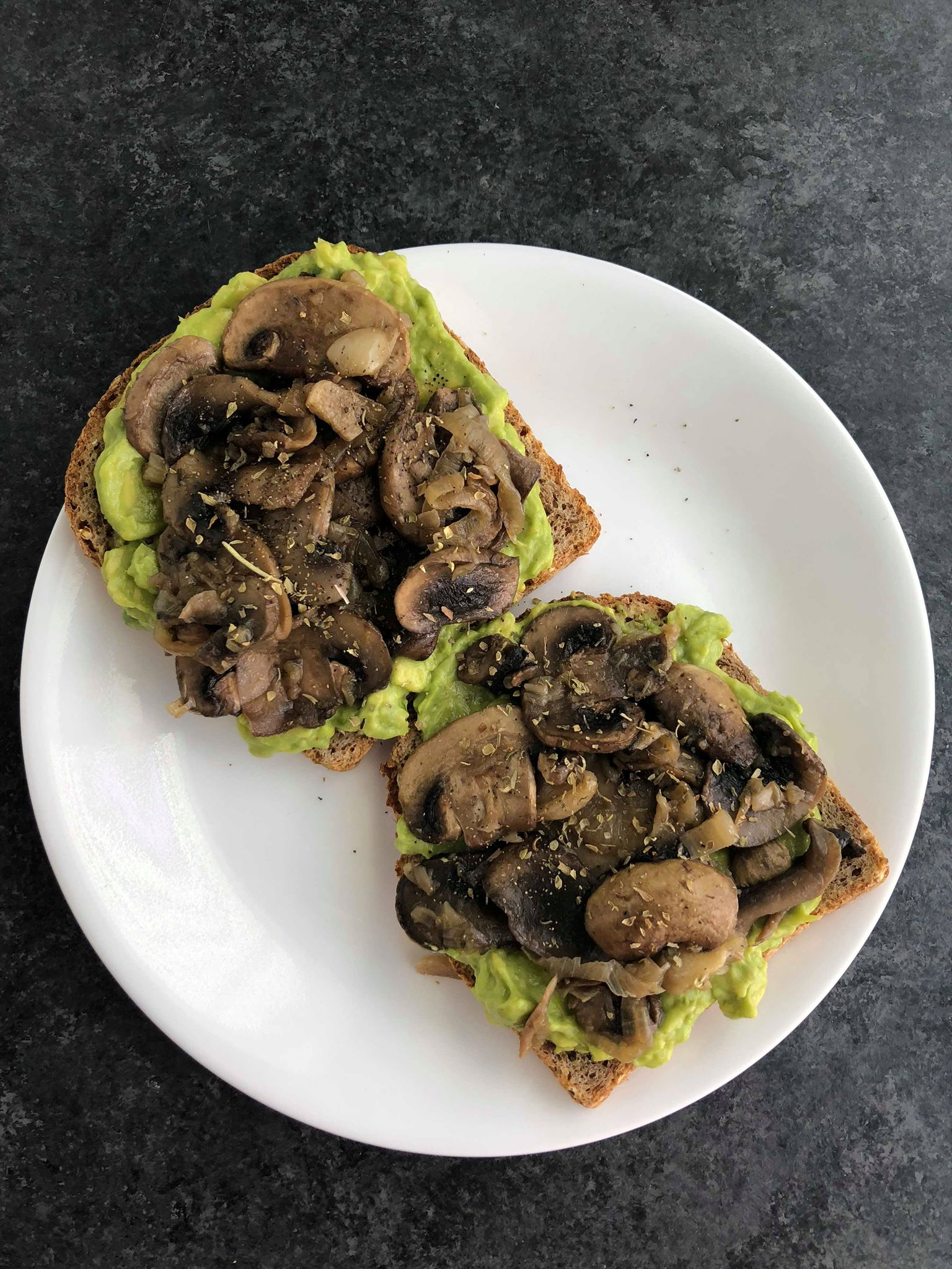 Two slices of avocado toast with mushrooms on top on a white plate with a dark background.