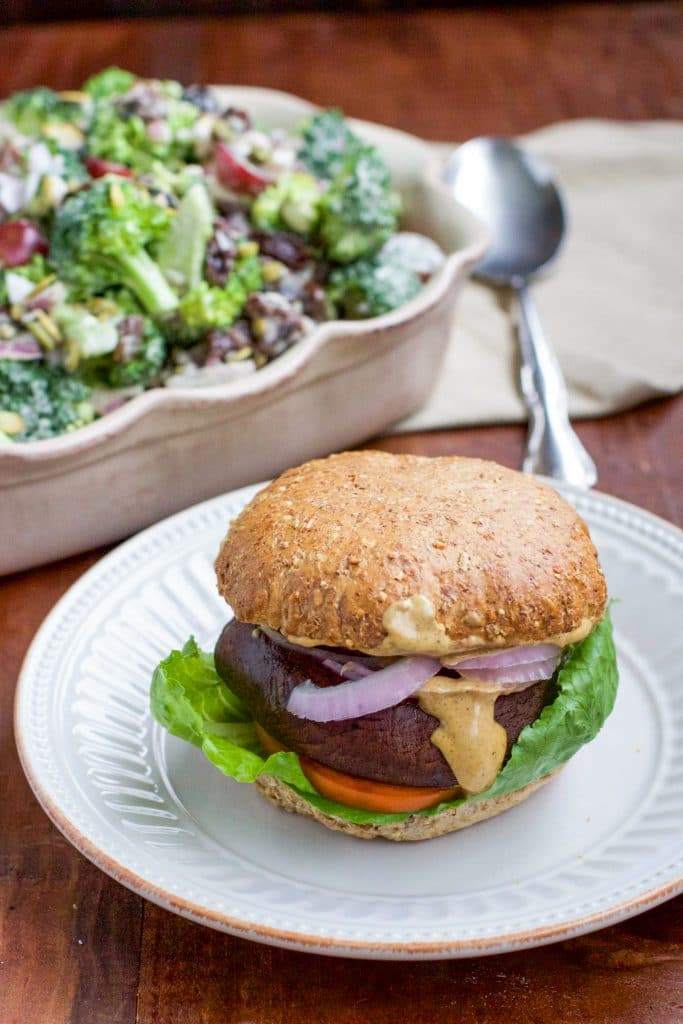 A portobellos mushroom burger on a white textured plate with a dish of vegan broccoli salad in the background sitting on a rustic table.