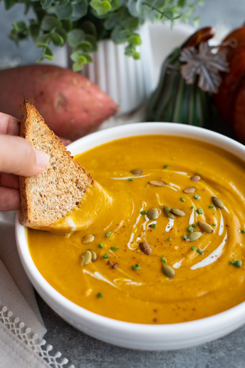 A hand dipping a piece of toasted bread into a bowl of soup next to a sweet potato.