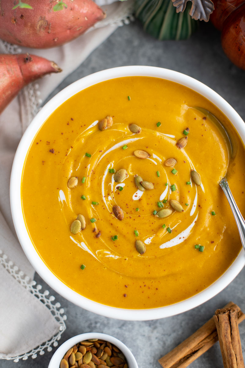A white bowl filled with pumpkin soup and a spoon on a gray background.