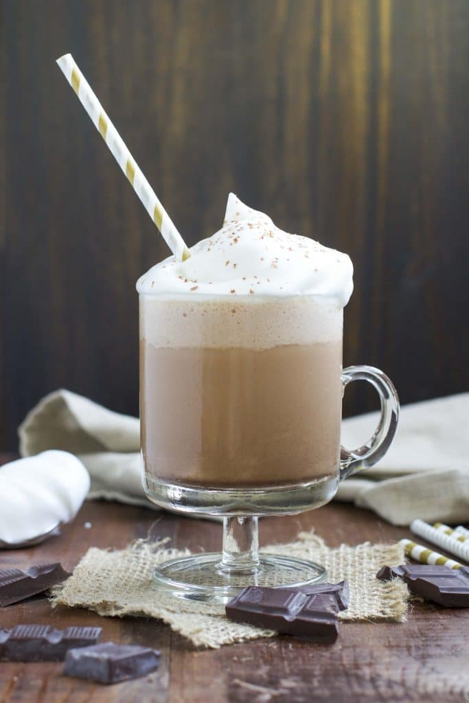A glass mug filled with a vegan Frappuccino topped with whipped cream next to chunks of chocolate on a rustic background.