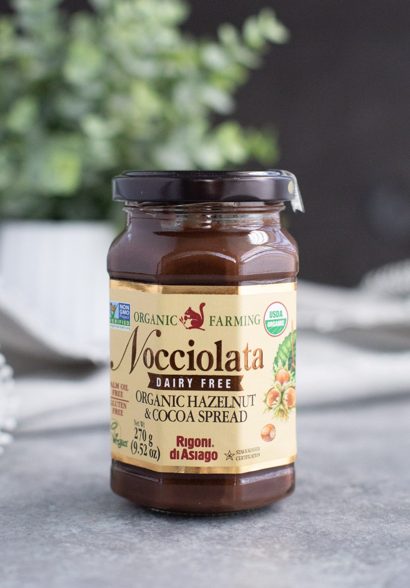 A jar of Nocciolata cocoa spread on a gray background.